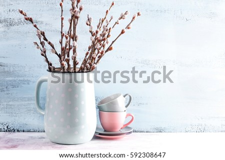 Home decor soft spring flowering willow in a vase on a light background, blooming willow in a jug on the table.