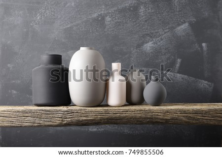 Home decor - various neutral colored vases on rough distressed wooden shelf against grey wall.