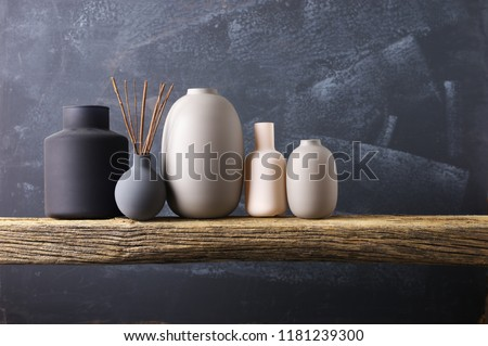 Home decor - various neutral colored vases with wood sticks on rough distressed wooden shelf against grey wall. #1181239300