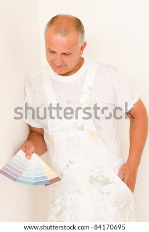 Home decorating mature male painter choose color swatches
