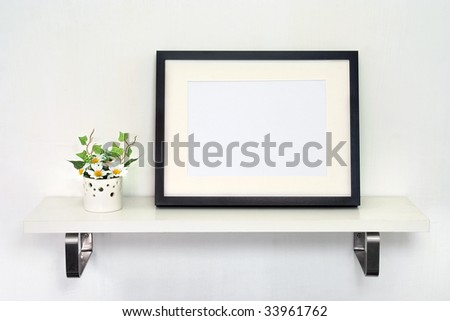Home Decoration Photo Frame. Potted daisies and a black photo frame on white shelf against a white wall.