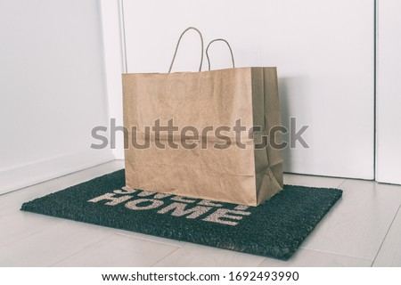 Home delivery of food grocery bag left at door mat for Corona virus spreading safety. Precaution measures against COVID-19, paper bag delivered without contact.