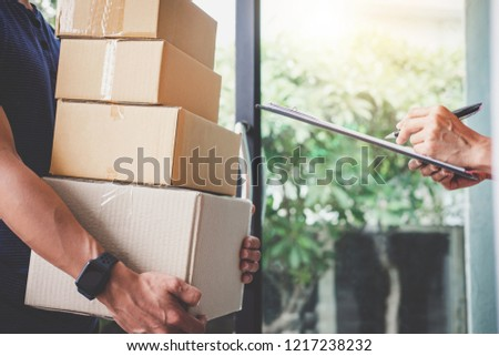 Home delivery service and working with service mind, Woman customer signing and receiving a cardboard boxes parcel from deliveryman. ストックフォト ©