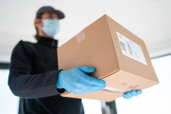 Home delivery shopping box man wearing gloves and protective mask delivering packages at door.