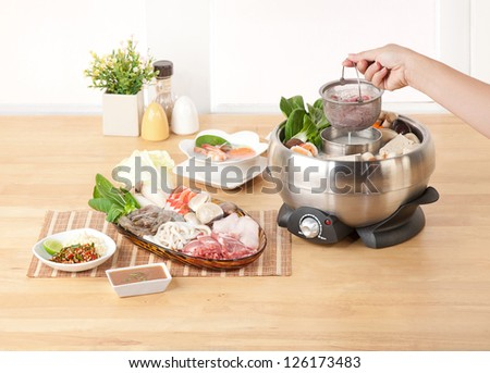Home electric appliance sukiyaki cooking pot in the kitchen interior