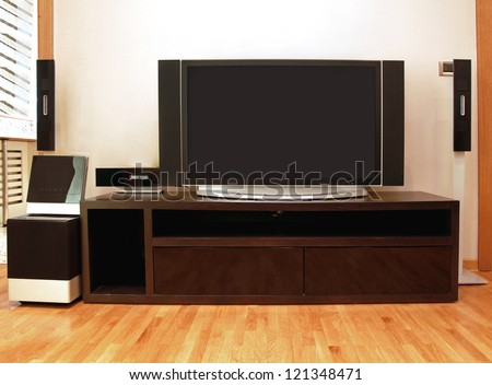 Home entertainment unit with plasma TV and surround speakers - stock photo