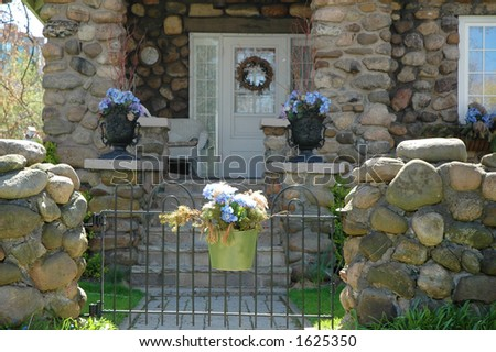 Home entrance to cobblestone house accented by purple blue hydrangea flowers in urns and a hanging pot on a gate - stock photo