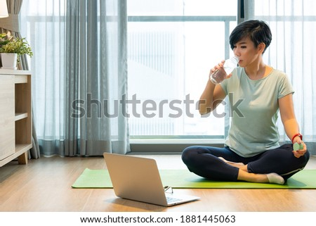 Home exercise during Covid 19 lock down. A healthy asian woman sit cross legs on a yoga mat, sip water from the bottle to keep her body stay hydrated. She watching online programs on laptop computer. Stok fotoğraf ©