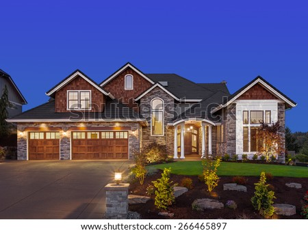 Home Exterior at Night: New Luxury House at Night with Deep Blue Sky, Three Car Garage, Columns, Gables, Green Lawn, Landscaping, and Driveway