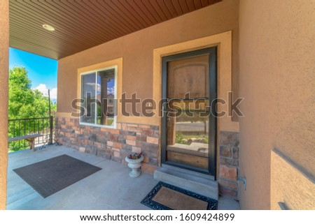 Home exterior view with porch and glass door in front of the brown front door