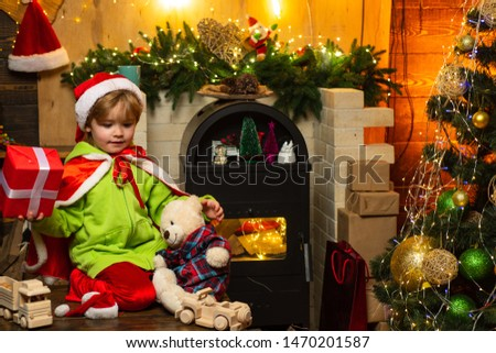 Home filled with joy and love. Make wish. Best wishes for you your family this christmas. Merry christmas and happy new year. Cute boy play near christmas tree. Kid enjoy winter holiday at home.
