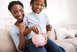 Home Finances Concept. Happy african kid putting coins into piggy bank, sitting on mom's lap, copyspace