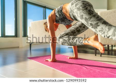 Home fitness woman doing yoga plank in living room on mat in small apartment- girl planking knee to opposite elbow plank yoga exercise getting in shape. High plank variation for core training.