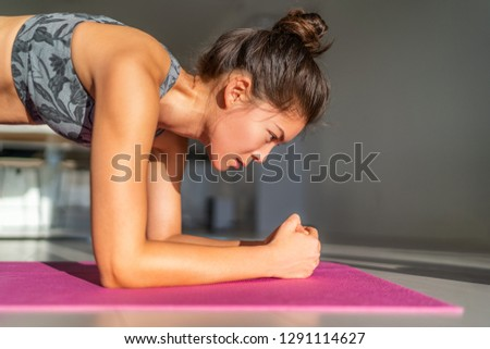 Home fitness, workout at home girl training indoors floor exercises on exercise mat in apartment condo. Asian woman planking doing bodyweight yoga. Core body.