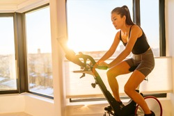 Home fitness workout woman training on smart stationary bike indoors watching screen connected online to live streaming subscription service for biking exercise. Young Asian woman athlete.