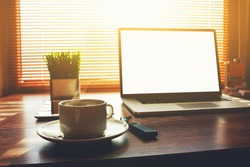 Home freelance desktop with open laptop computer, cup of coffee, digital tablet and green plant lying on the table, business person net-book with blank screen for information content or text message