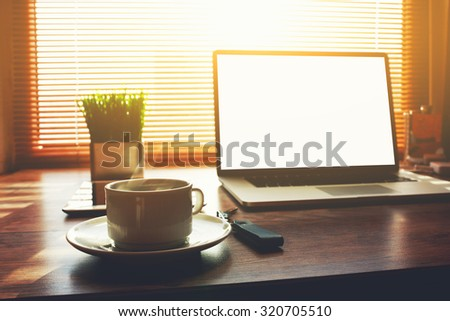 Home freelance desktop with open laptop computer, cup of coffee, digital tablet and green plant lying on the table, business person net-book with blank screen for information content or text message ストックフォト ©
