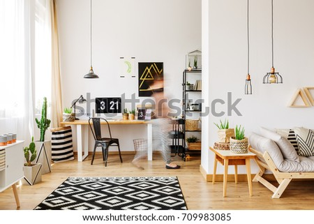Home furniture of a freelancer with natural eco accessories, wooden desk, potted plants, patterned rug, computer and triangle shelves in spacious living room #709983085