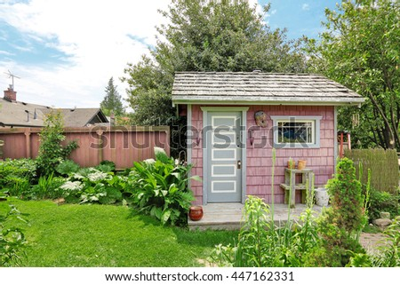 Home garden on backyard with small red barn shed and red wooden fence
