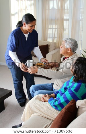 Home health care worker and an elderly couple - stock photo