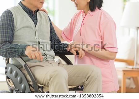 Home helper carer and senior man in wheelchair ストックフォト ©