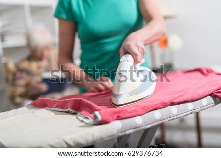 Home helper ironing clothes for elderly woman ストックフォト ©