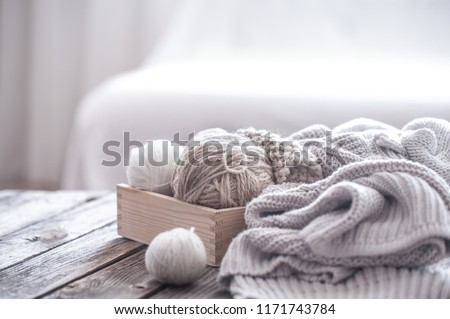 home hobbies, cozy knitted sweaters with a ball of yarn in the living room on a wooden background #1171743784