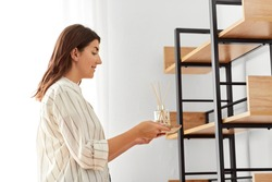 home improvement, decoration and people concept - happy smiling woman placing aroma reed diffuser to shelf