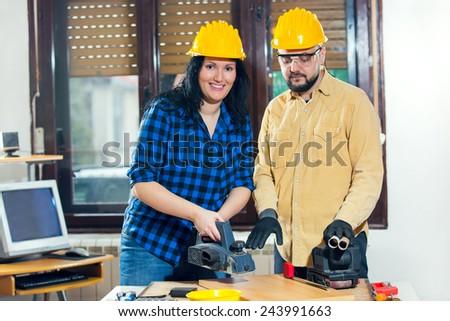 Home improvement - handy woman sanding wooden floor in workshop, handy man assisting, selective focus