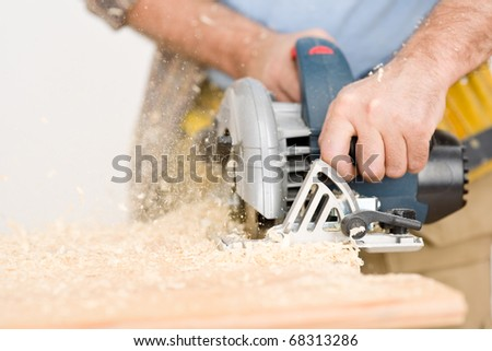 Home improvement - handyman cut wood with jigsaw in workshop