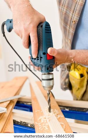 Home improvement - handyman drilling wood in workshop