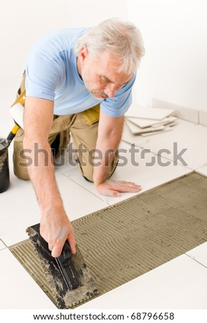 Home improvement, renovation - handyman laying tile, trowel with mortar