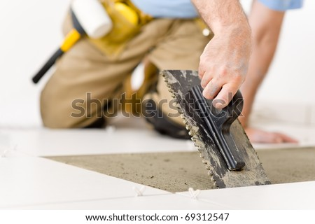 Home Renovation on Home Improvement  Renovation   Handyman Laying Tile  Trowel With