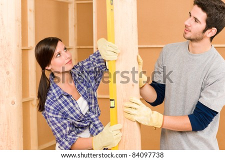 Home improvement smiling young couple fixing wall with spirit level