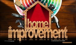 Home improvement - Wooden symbol in the shape of a house with a work tools and a color palette on a wooden desk