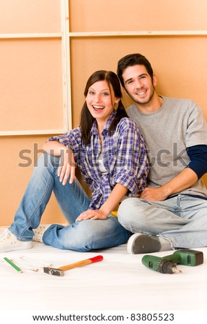 Home improvement young cheerful couple repair tool relax on floor