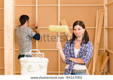 Home improvement: young happy couple fixing new house renovating wall