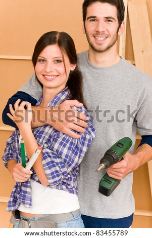 Home improvement young happy couple with repair tool hand drill ruler