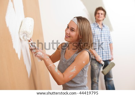 Home improvement: Young man and woman painting wall with paint roller