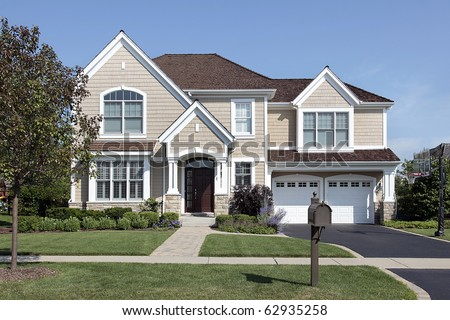Home in suburbs with arched entry and brown cedar roof
