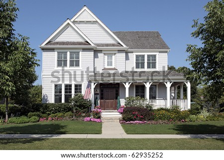 Home in suburbs with flowers and front porch