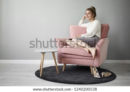 Home interior and furniture concept. Horizontal picture of stylish trendy looking young business lady dressed in fashionable wear having relaxed look while resting indoors in comfortable armchair