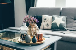 Home interior decor in gray and brown colors: glass jar with dried flowers, vase and candle on the wooden tray on the coffee table over sofa with cushions. Living room decoration.