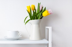 home interior decoration: a bouquet of tulips in a jug and a cup and saucer on white shelves