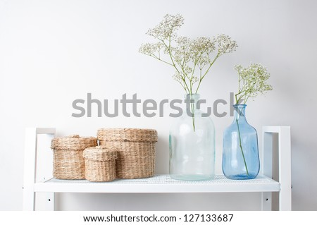 home interior decoration: the branches in vintage bottles and baskets on white shelves
