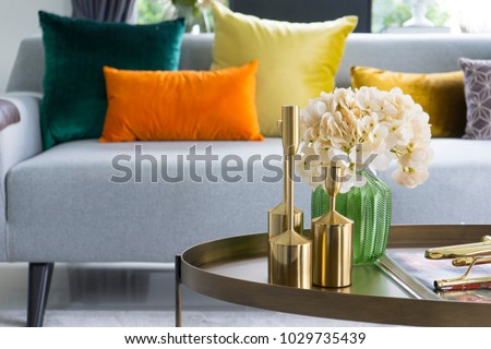Home interior decorative item on table with glass jar and dried flowers, candle.  Colorful cushions on grey sofa.