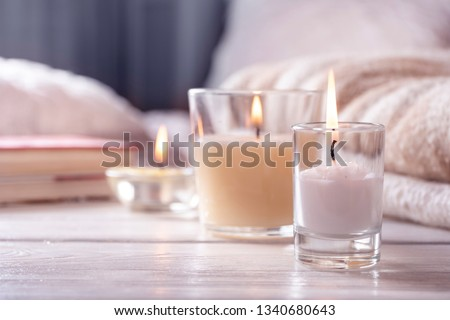 Home interior. Still life with detailes. Several candles on white wooden table in front of bed, the concept of cosiness. Close up.