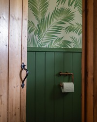 Home interior view through doorway into small bathroom downstairs loo or closet.  Shows green colour scheme with paint and wallpaper and bespoke loo roll holder