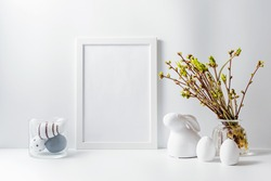 Home interior with easter decor. Mockup with a white frame and green buds on branches in a vase on a light background