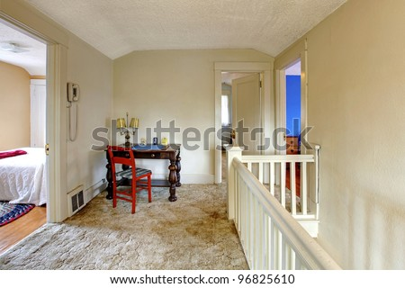 Home interior with old writing desk with red chair.